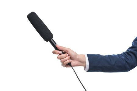 cropped view of female hand holding microphone for interview, isolated on white Stock Photo