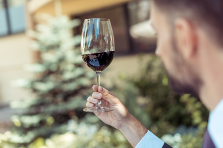 Close-up portrait of handsome man sommelier tasting glass of red wine, focus on wine