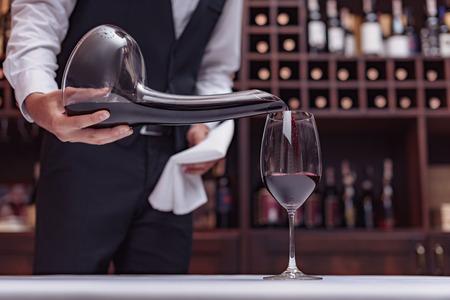 Przycięty widok sommeliera wlewającego czerwone wino z karafki do szklanki przy stole w piwnicy