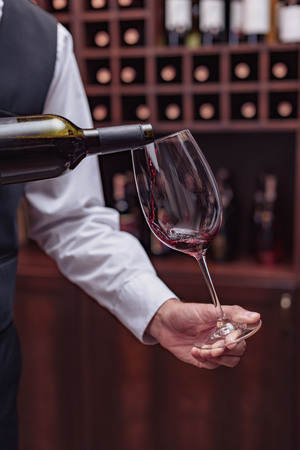 Cropped view sommelier pouring red wine from bottle into glass at table in cellar Banco de Imagens