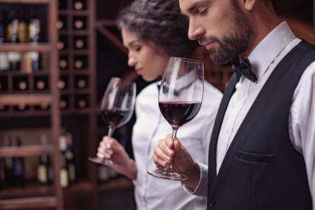 Dos sumilleres, hombres y mujeres, degustación de vino tinto en bodega.
