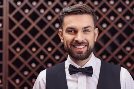 Portrait of young handsome sommelier standing in wine cellar Banco de Imagens