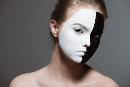 young stylish girl with creative white and black bodyart on face looking at camera, isolated on grey