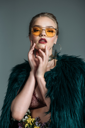 young seductive attractive model posing in green fur coat and orange sunglasses for fashion shoot, isolated on grey Stock Photo