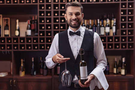 Portrait of handsome sommelier holding bottle of wine and glass in cellar