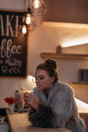 seductive fashionable young woman in fur coat smoking cigarette at bar counter