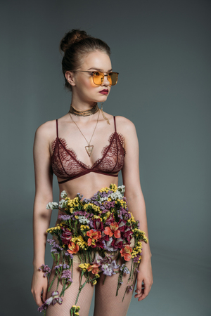 young sensual beautiful girl posing in floral skirt, lace bra and orange sunglasses for fashion shoot, isolated on grey Standard-Bild - 102893826
