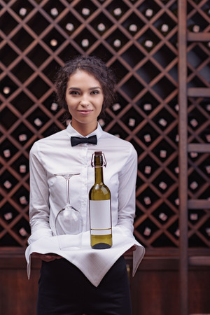 Close-up woman sommelier standing with bottle of wine and glass on tray in cellar Banco de Imagens