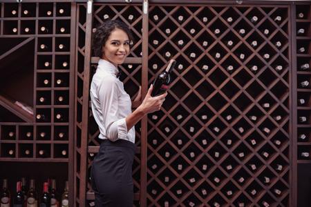 Portrait of young beautiful woman sommelier choosing wine in cellar
