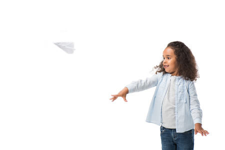 cute smiling african american girl throwing paper plane isolated on white
