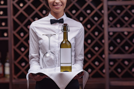 Cropped view woman sommelier standing with bottle of wine and glass on tray in cellar Banco de Imagens