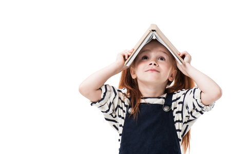 Jolie petite écolière rousse tenant un livre au-dessus de la tête et levant isolé sur blanc Banque d'images