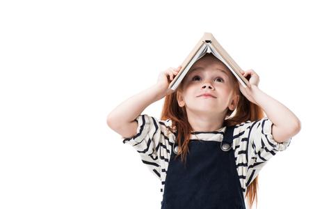 Linda colegiala pelirroja sosteniendo un libro sobre la cabeza y mirando hacia arriba aislado en blanco Foto de archivo