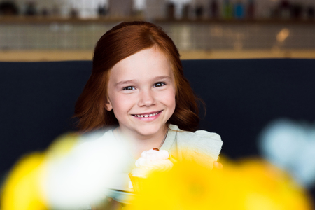portrait of adorable happy redhead girl holding cupcake and smiling at camera in cafe