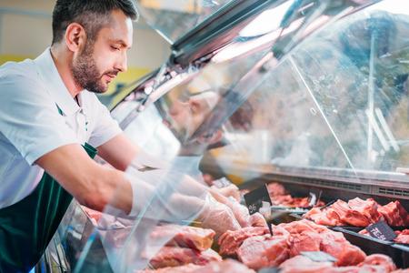 Verkäuferin im Vorfeld, die frisches rohes Fleisch im Supermarkt sortiert