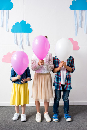 cute little kids holding balloons while standing together at birthday party Stock Photo