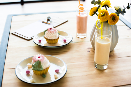 close-up view of delicious cupcakes on plates and milkshakes in glasses on wooden table
