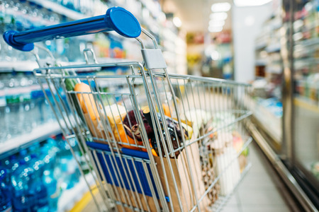 selective focus of shopping cart with purchases in supermarket