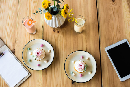 top view of blank clipboard, tasty cupcakes on plates, milkshakes and digital tablet on wooden table