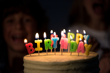 close-up view of delicious birthday cake with burning candles in dark room