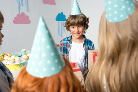 cropped shot of kids presenting birthday gifts to cute smiling boy