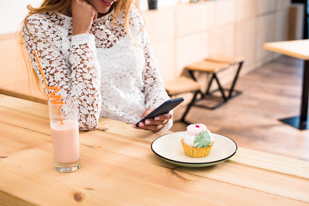cropped shot of young stylish woman using smartphone while eating cupcake and drinking milkshake in cafe Banque d'images - 102278991