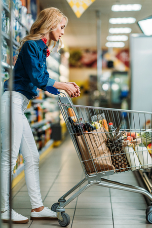 side view of young woman looking at purchases in shopping cart in supermarket Stok Fotoğraf