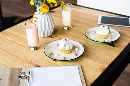 close-up view of blank clipboard, tasty cupcakes on plates, milkshakes and digital tablet on wooden table
