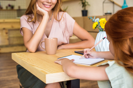 cropped shot of smiling young mother looking at cute little daughter drawing with pencil in cafe