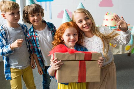 adorable happy kids holding gifts while standing together at birthday party Stock Photo