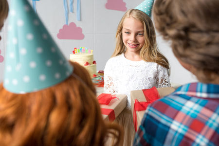 cropped shot of kids presenting gifts to cute happy girl at birthday party