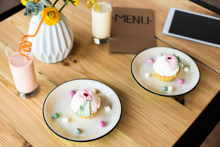 close-up view of delicious cupcakes, milkshakes , digital tablet and menu on table in cafe Stock Photo