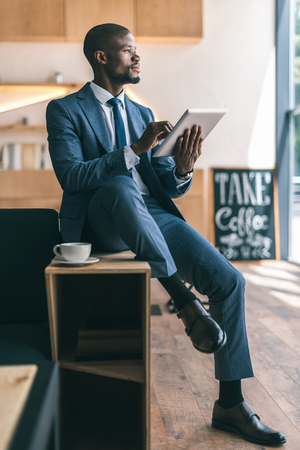 handsome thoughtful african american businessman using digital tablet during coffee break in cafe
