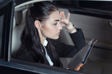 Young dissatisfried woman in suit sitting in backseat of a car with digital tablet Stock Photo