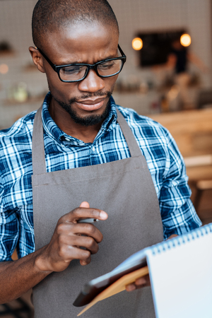portrait of handsome african american waiter taking order with notepad in coffee shop