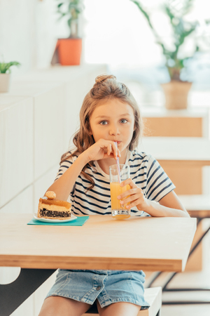 cute little girl with cake and orange juice sitting in cafe Фото со стока
