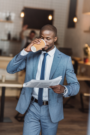 handsome african american businessman drinking coffee and reading newspaper Foto de archivo - 102355305