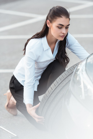 Young attractive woman in formal wear holding a spare car tire in parking lot
