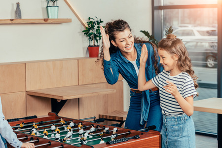 mother and daughter celebrating win in table football 스톡 콘텐츠
