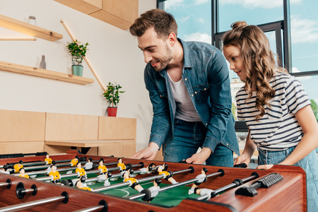 happy young father and daughter playing table football