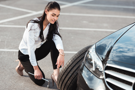 Young attractive woman in formal wear squatting near car tire with lug wrench in her hand