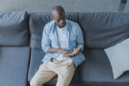 Handsome african american man reading book at home Banco de Imagens