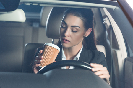 Young attractive woman in suit driving a car and drinking a cup of coffee