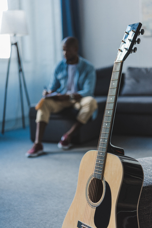 Close-up view acoustic guitar standing in room and African american musician sitting on background and writing new song Stock Photo