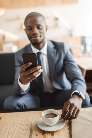 handsome african american businessman using smartphone during coffee break in cafe  Stock Photo