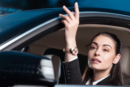 Young attractive woman in suit calling someone while sitting in drivers seat of passenger car