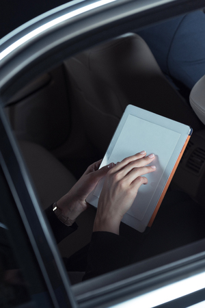 Cropped shot of a woman sitting in backseat of passenger car and using digital tablet