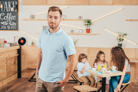 young handsome man standing in cafe with his family blurred on background Stock Photo - 102355436