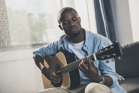 African american man playing acoustic guitar at home Stock Photo
