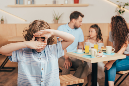 curly boy in cafe making frame of hands with his happy family blurred on background Stock Photo